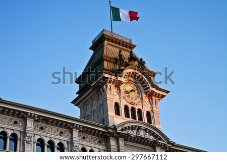 Trieste, Italy - Unity of Italy Square, architectural detail of City Hall  tower surmounted by Italian flag, view of  clock, quarter bell with bronze figure at sunset