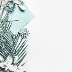 Tropical leaves with orchid flowers, pastel blue envelope, and succulent decoration on white desktop background, top view, border