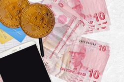 10 Turkish liras bills and golden bitcoins with smartphone and credit cards. Cryptocurrency investment concept. Crypto mining or trading