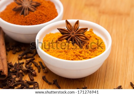 Turmeric powder in white bowl with anise flower on top, on wooden table background