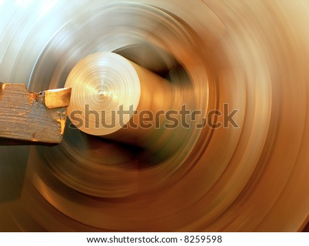 Turning lathe in action is processing metal bar - with motion blur