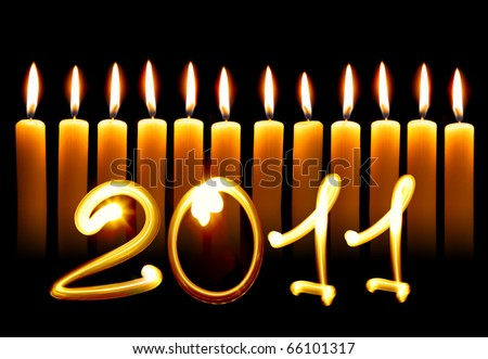 2011 - Twelve alight candles over black background - stock photo