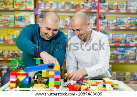 Two adult men with happy faces create colorful constructions of toy bricks. Two adult men build of plastic blocks.