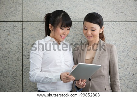 Two Asian women using a digital tablet PC.