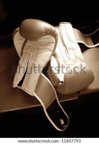 two boxing gloves in sepia, isolated on black background