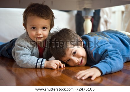 Two brothers playing on the floor.