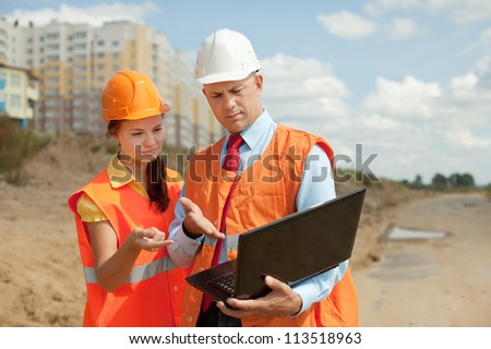 two builders wearing protective helmet works on the building site