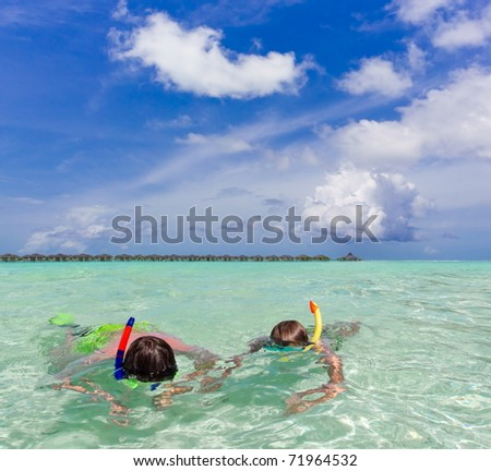 Two children snorkeling in the ocean.
