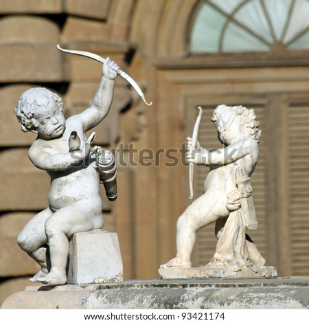 Two Cupids with  bow, statues from Boboli Gardens in Florence, Italy, Europe - stock photo