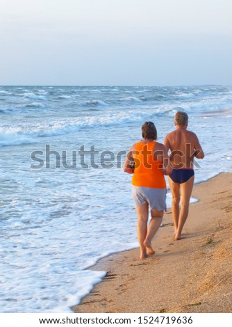 two elderly people a man and a woman boog along the sea beach        Stockfoto ©