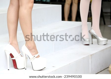 Two Female legs stand on staircase in white high heel shoes and silver high heel shoes