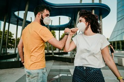 Two friends reuniting after a long time after the quarantine caused by the covid19. They wear a surgical mask and greet each other with the elbow. New normal