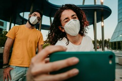 Two friends reuniting after a long time after the quarantine caused by the covid19. They wear a surgical mask and take photos together with social distance