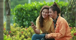 Two friends taking photo selfie with smartphone outdoors. Millennial young women posing to camera