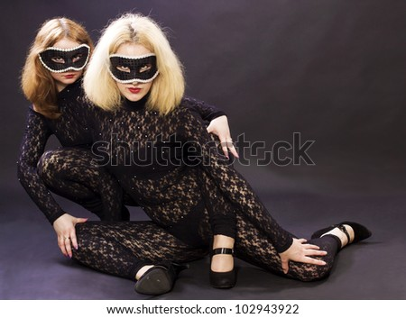 Two girls in masks on a black background