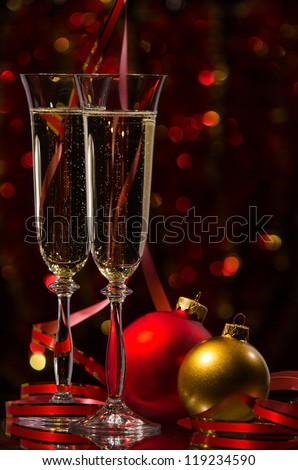 Two glasses of champagne on the background of Christmas lights with balls