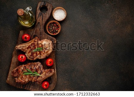 two grilled beef steaks with spices on a stone background with copy space for your text