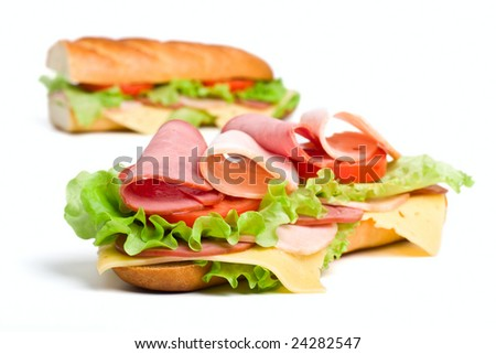 two halves of long baguette sandwich with lettuce, tomatoes, ham, turkey breast and cheese