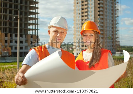 two happy builders in hardhat works on the building site