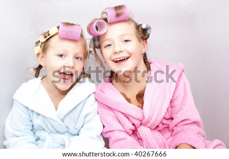 Two little sisters are in bath robes and home with curlers hairdo on the head.