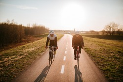 Two middle-aged men ride a bicycle on a road