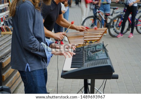 Two musicians on the street on a warm summer day. Digital piano and the traditional Xylophone. People around listen to music .            #1489693967
