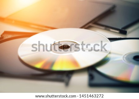 Two new compact disks lie next to the black boxes from the disks, and is illuminated by bright sunlight, from which the disks shimmer in different colors. #1451463272