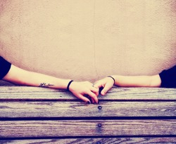 two people holding hands on a bench toned with a retro vintage instagram filter effect app or action