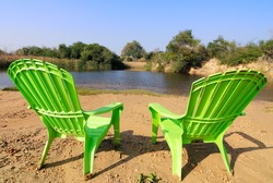 two plastic chairs on beach of relaxing lake