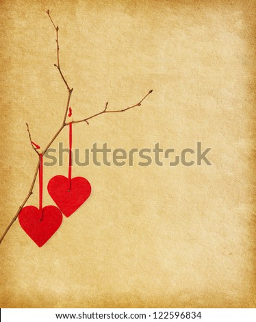 two red hearts, hanging on a branch over the paper background.