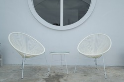 Two wicker chairs with congret wall as backdrop