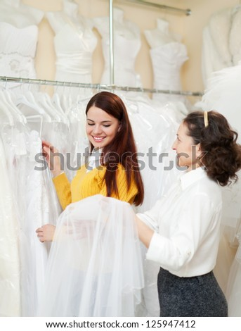 Two women  at wedding store. Focus on young bride