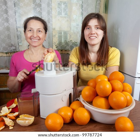 Two women  making fresh orange juice in home kitchen