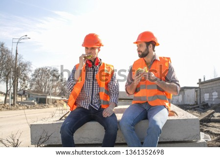 two workers in helmets lunch, rest, sit on concrete slabs #1361352698
