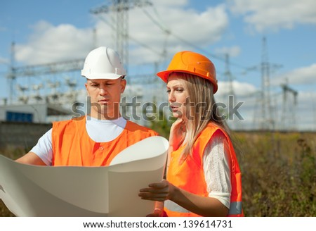 two workers wearing protective helmet works at electrical power station.