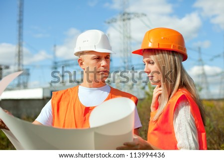 two workers wearing protective helmet works at electrical power station. Focus on man - stock photo