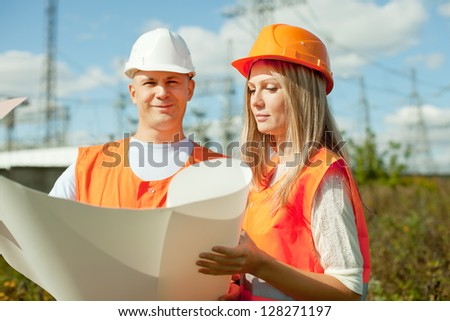 two workers wearing protective helmet works at electrical power station, Focus on woman