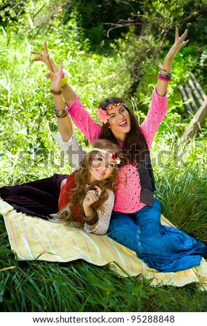 Two young beautiful girls hippie have fun laying in a lawn - stock photo