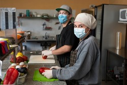 two young entrepreneurs cooking and handling food with chinstrap and gloves for precaution