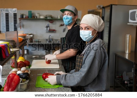 two young entrepreneurs cooking and handling food with chinstrap and gloves for precaution Foto stock ©