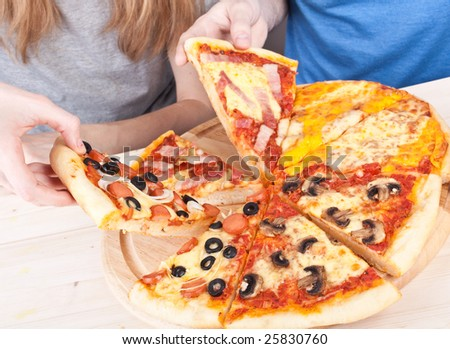 two young people eating pizza