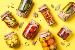 ?ucumber, squash and tomatoes pickling and canning into glass jars. Ingredients for vegetables preserving. Healthy fermented food concept. Top view. Copy space