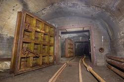 Underground abandoned iron ore mine tunnel with massive doors