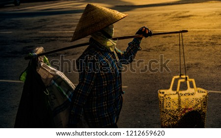 unrecognizable Vietnamese with conical hat carries a yoke on her shoulder along the street. Profile wiew of a human with conical hat in contrast sunset light.