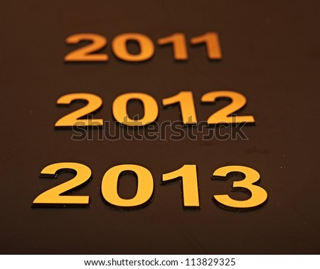 Upcoming years 2011, 2012 and 2013 as golden digits over dark background