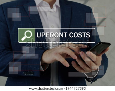 UPFRONT COSTS text in search bar. Loan officer looking for something at cellphone. Anupfront costis an initial sum of money owed in a purchase or business venture. Сток-фото ©