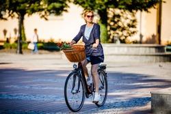 Urban biking - woman riding bike on city street