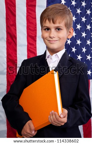 Ã?Â??ute schoolboy is holding an orange book against USA flag