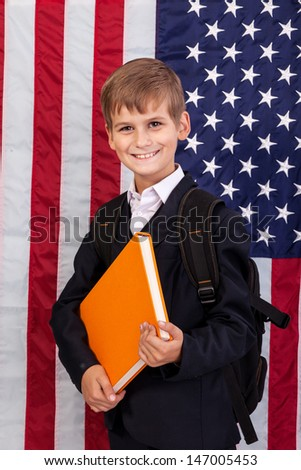 �������¡ute schoolboy is holding an orange book against USA flag