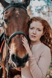 Аuthentic portrait of beautiful redhaired woman with horse outdoors.